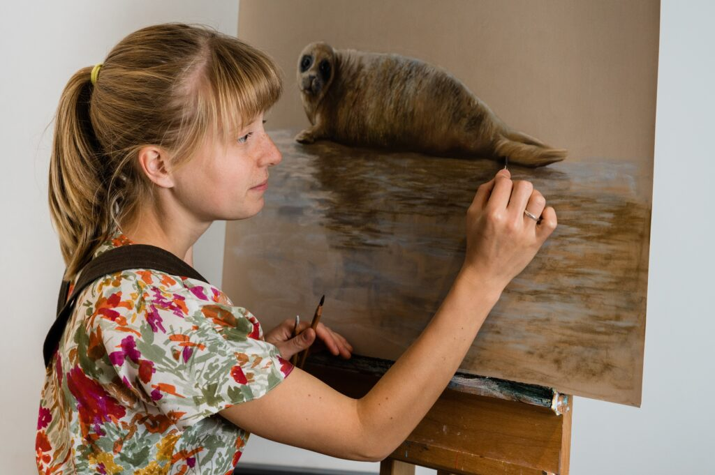 pastel pencil artist working on original seal painting